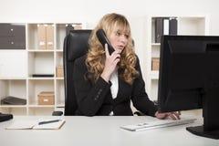 Mulher de negócios que fala no telefone ao datilografar foto de stock