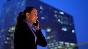 Mulher de negócios que fala no telefone celular contra o arranha-céus na baixa video estoque