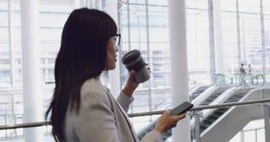 Mulher de negócios que fala no telefone celular e que anda na entrada no escritório 4k filme