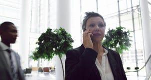 Mulher de negócios que fala no telefone celular na entrada no escritório 4k vídeos de arquivo