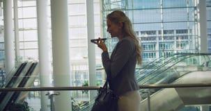 Mulher de negócios que fala no telefone celular na entrada no escritório 4k video estoque