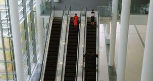 Mulher de negócios que fala no telefone celular na escada rolante 4k video estoque