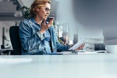 Mulher de negócios que fala no telefone esperto com cliente Fotografia de Stock