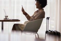 Mulher de negócios que faz a chamada video na sala de estar do aeroporto foto de stock royalty free