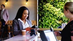 Mulher de negócios que faz o pagamento com NFC vídeos de arquivo