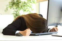 Mulher de negócios que golpeia a cabeça contra a tabela imagens de stock royalty free