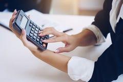 A mulher de negócios que guarda a calculadora para calcula o número e o disco fotos de stock