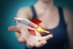 Mulher de negócios que guarda e que toca em uma rendição do foguete 3D Fotografia de Stock Royalty Free