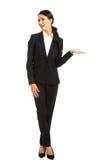 Mulher de negócios que guarda o copyspace na mão esquerda Foto de Stock