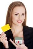 Mulher de negócios que guarda o modelo da casa e o cartão amarelo Fotografia de Stock