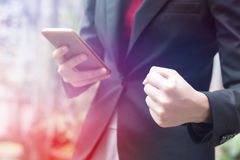 Mulher de negócios que guarda o punho ao olhar o smartphone Imagens de Stock Royalty Free