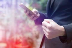 Mulher de negócios que guarda o punho ao olhar o smartphone Fotografia de Stock