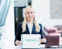 Mulher de negócios que guarda o sinal do dinheiro Foto de Stock