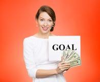Mulher de negócios que guarda o sinal e o dinheiro do objetivo Imagem de Stock