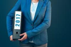 Mulher de negócios que guarda a pasta de 2017 originais com arquivos arquivados Imagem de Stock Royalty Free