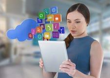 Mulher de negócios que guarda a tabuleta com ícones dos apps da nuvem no salão brilhante do espaço Fotografia de Stock Royalty Free