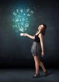 Mulher de negócios que guarda um copo branco com ícones do negócio Fotografia de Stock Royalty Free