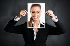 Mulher de negócios que guarda uma imagem dsi mesma, mostrando a atitude positiva imagem de stock royalty free