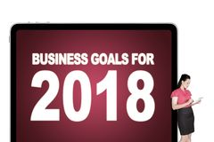 Mulher de negócios que guarda uma tabuleta digital que inclina 2018 palavras dos objetivos de negócios no quadro de avisos imagem de stock