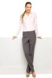 Mulher de negócios que inclina-se de encontro ao quadro de avisos em branco Foto de Stock