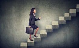 Mulher de negócios que intensifica uma escada da carreira da escadaria fotografia de stock