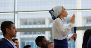 Mulher de negócios que interage com o orador no seminark 4k do negócio video estoque