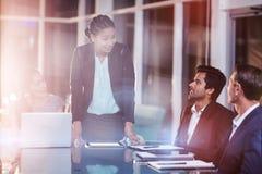 Mulher de negócios que interage com os colegas de trabalho na reunião Imagens de Stock Royalty Free