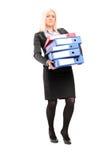 Mulher de negócios que leva uma pilha dos dobradores Foto de Stock Royalty Free