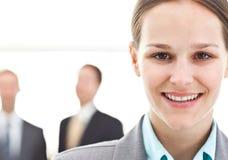 Mulher de negócios que levanta na frente de dois homens de negócios Imagens de Stock