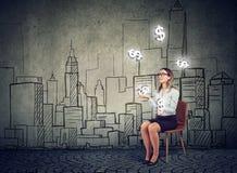 Mulher de negócios que manipula com símbolos do dólar em um fundo da arquitetura da cidade foto de stock