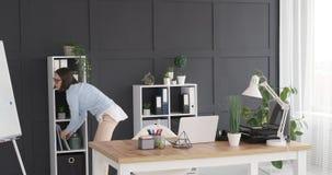 Mulher de negócios que mantém o arquivo na prateleira e que retorna a sua mesa de escritório video estoque