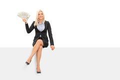 Mulher de negócios que mantém o dinheiro assentado em um painel Imagens de Stock