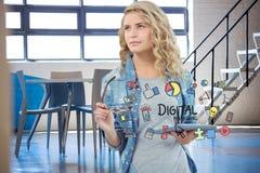 Mulher de negócios que mantém o PC da tabuleta cercado pelo texto e por ícones digitais do mercado fotografia de stock royalty free