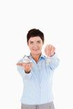 Mulher de negócios que mostra chaves e uma casa diminuta Fotos de Stock Royalty Free