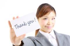 A mulher de negócios que mostra um cartão com palavra agradece-lhe Fotografia de Stock Royalty Free