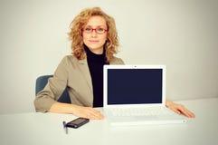 Mulher de negócios que mostra uma tela do portátil Imagens de Stock Royalty Free