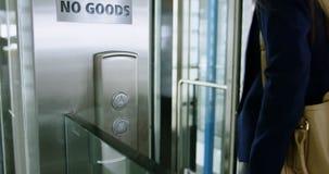 Mulher de negócios que obtém no elevador 4k video estoque