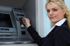 Mulher de negócios que obtém o dinheiro do cartão de crédito no ATM imagens de stock