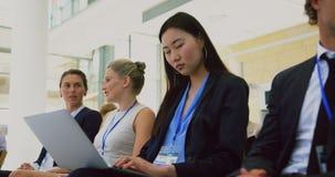 Mulher de negócios que olha a câmera durante o seminário 4k filme