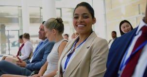 Mulher de negócios que olha a câmera durante o seminário 4k vídeos de arquivo