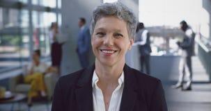 Mulher de negócios que olha a câmera na entrada no escritório 4k vídeos de arquivo