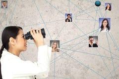 Mulher de negócios que olha candidatos através dos binóculos fotografia de stock royalty free