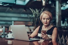 Mulher de negócios que olha no telefone e que trabalha tarde imagens de stock royalty free
