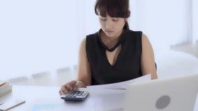Mulher de negócios que olha o papel de carta do gráfico e para calcular a finança das despesas com estatística e calculadora filme
