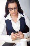 Mulher de negócios que olha o telefone móvel Fotografia de Stock Royalty Free