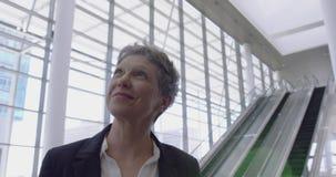 Mulher de negócios que olha para cima na entrada no escritório 4k video estoque