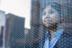 Mulher de negócios que olha para fora através da janela, reflexão da cidade no vidro Imagens de Stock Royalty Free
