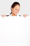 Mulher de negócios que olha a placa branca imagem de stock