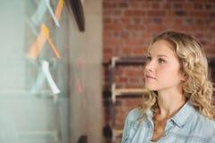 Mulher de negócios que olha a placa de vidro no escritório criativo imagem de stock