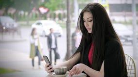 Mulher de negócios que olha seu telefone que senta-se no terraço com um copo do chá no fundo da cidade filme